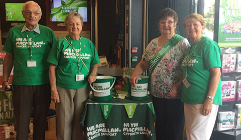 Four older fundraisers wearing green Macmillan tees standing by a fundraising table inside a local Argos shop.