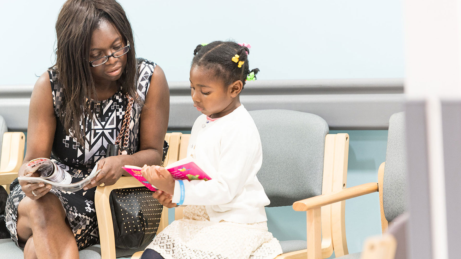 Deanne sitting in a hospital waiting room reading with her young daughter.