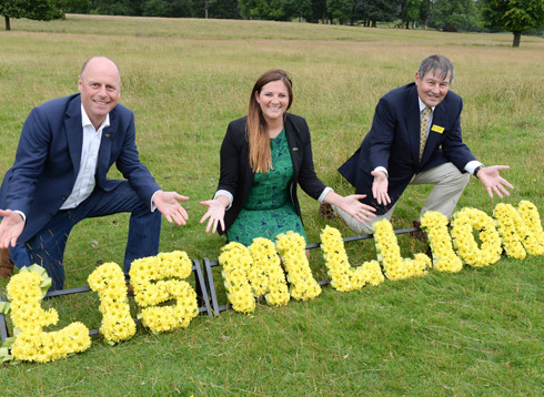 Three people who kneeling down on the grass presenting a flower arrangment that spells the words '£15 million'