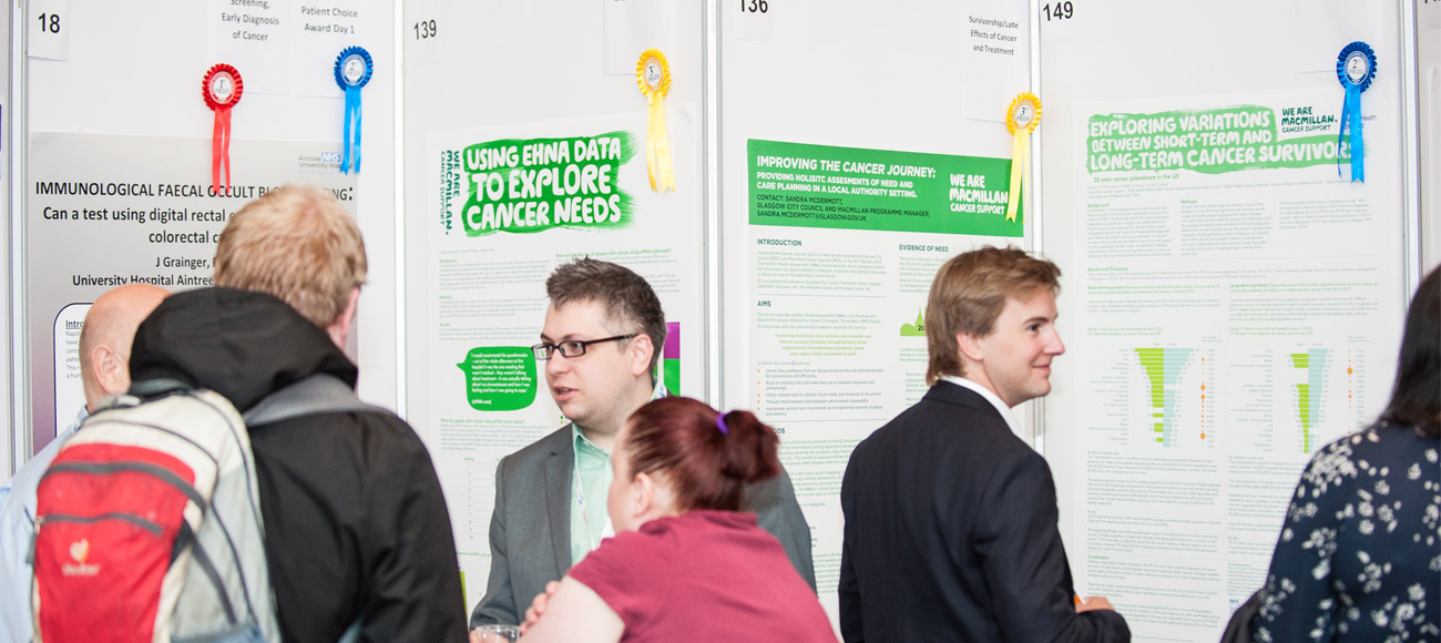 A group of people mingle in front of a display of winning evidence posters at a conference