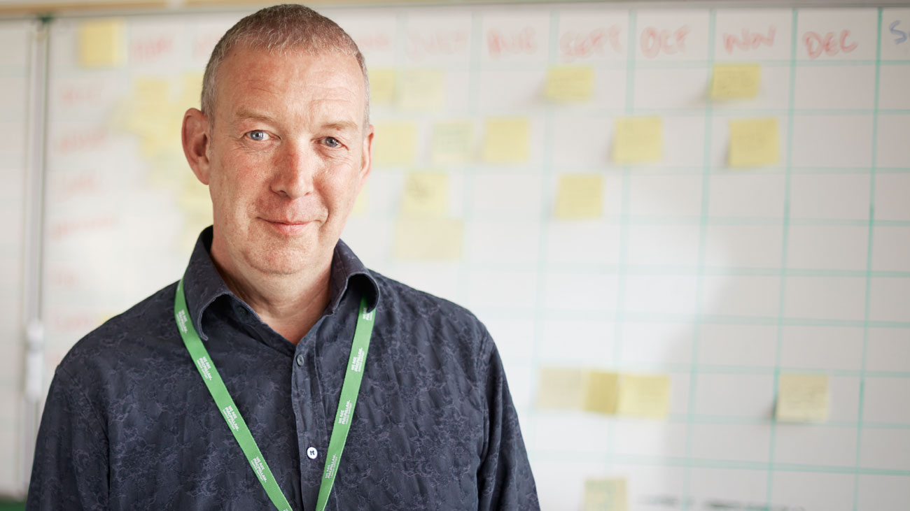 Michael,  Macmillan's Online Community Manager, is standing in front of a whiteboard covered in post-it notes.