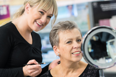 A Boots Macmillan Beauty Advisor applies eye liner to a woman going through cancer treatment.