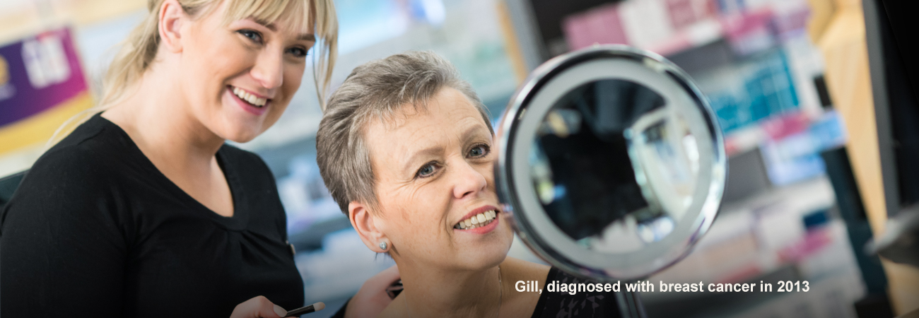 Gill, diagnosed with cancer, sits having eye make-up done by a Boots Macmillan Beauty Advisor.