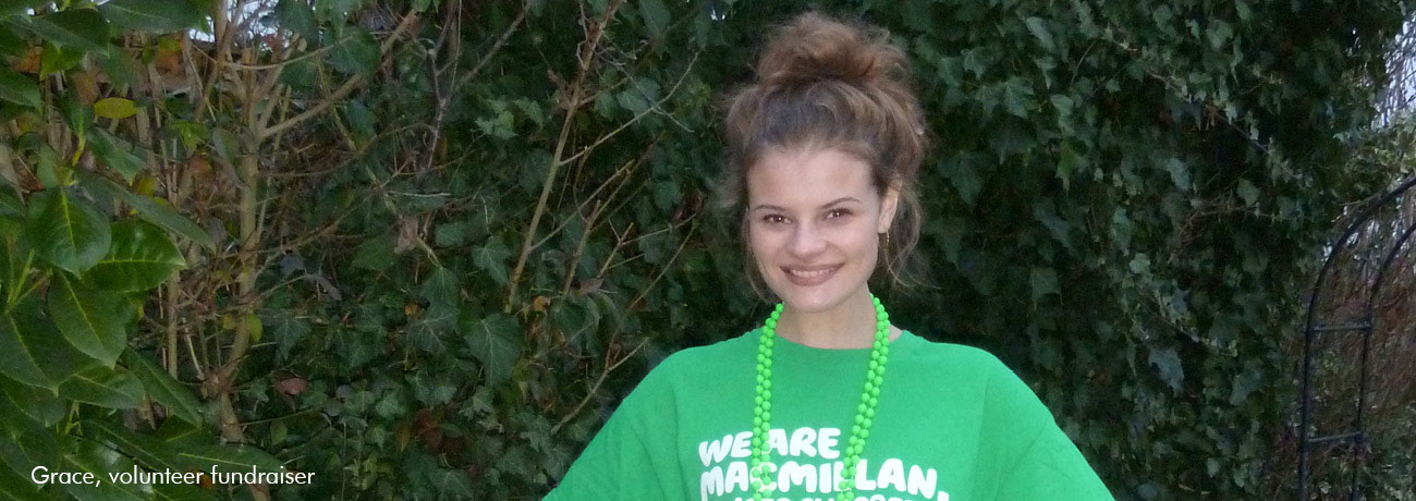 A young girl smiles in an outdoor setting. She wears a green Macmillan T-shirt.