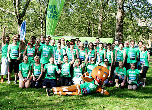 Macmillan fundraisers pose for a photo. A person is dressed as a gingerbread person.
