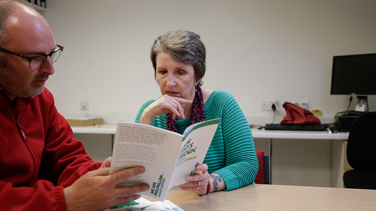 Cath reads a Macmillan booklet with her manager at her workplace. The booklet is about her rights at work.
