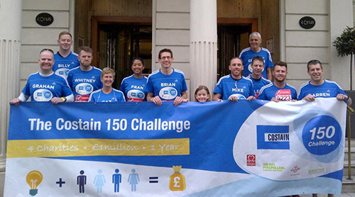 A group of Costain employees standing behind a banner with the words 'Costain, 150 challenge'