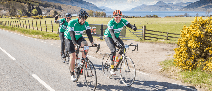 Three men wearing green Macmillan cycling vests riding on a road in front of Loch Ness.