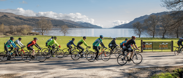 12 cyclists, two of which are wearing green Macmillan cycling vests riding past Loch Ness.
