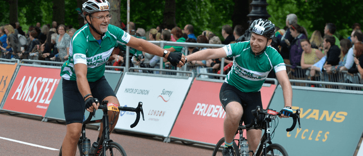 An older and younger man wearing green Macmillan cycling vests holding hands as they ride towards the finish line.