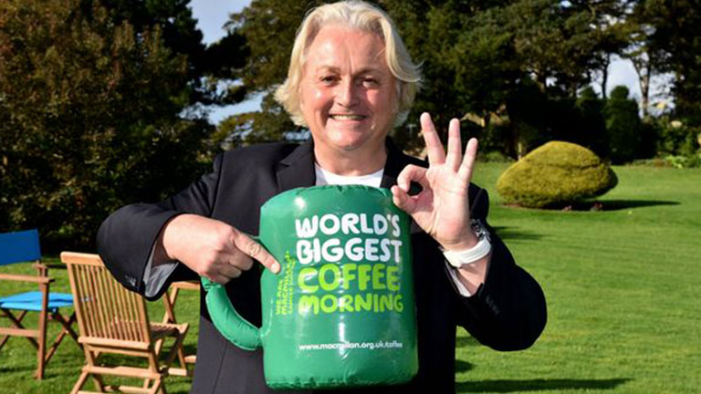 Celebrity fashion designer David Emanuel smiling and holding an inflatable plastic mug. The words, 'World's Biggest Coffee Morning' are on the mug.