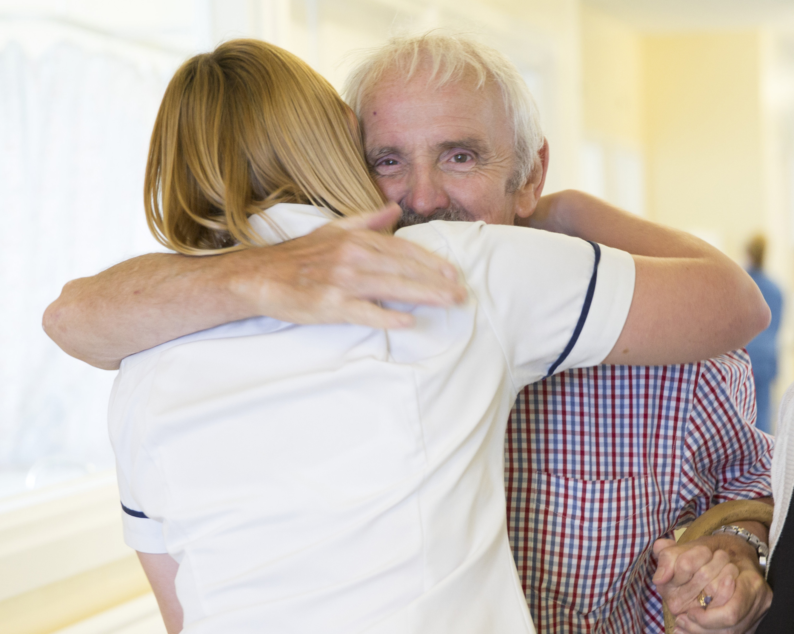 David Phillips, a man with white hair and grey moustache, can be seen looking over the shoulder of his physiotherapist Kathy who is giving him a hug.