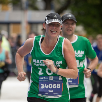 Two Team Macmillan runners wearing green running vests and black baseball caps