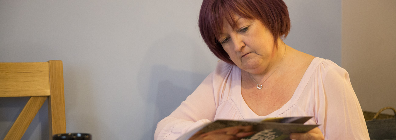 Marie, a Macmillan campaigner, reading a macmillan publication.