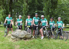 7 cyclists standing wearing green Macmillan cycling jerseys, standing next to their bikes on the side of the road.