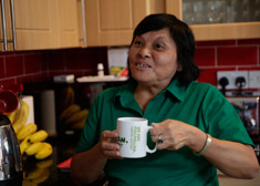 A middle aged woman with shoulder length dark hair, wearing a dark green polo shirt, smiling and holding a cup of tea.