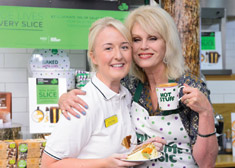 A Macmillan professional and Joanna Lumley standing together with cups of tea in their hands at a Coffee Morning.