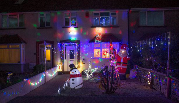 A terraced house that has been decorated for Christmas with Christmas, an inflatable snowman and an inflatable Santa.