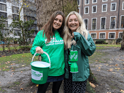 Two young women wearing green. One holding a Macmillan collection bucket and the other a collection tin.