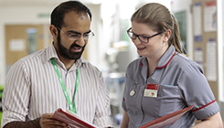 Two healthcare professionals looking at a booklet