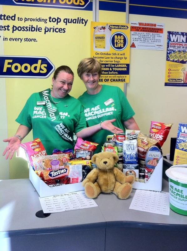 Two women in Macmillan t-shirts standing behind a stall raising money.