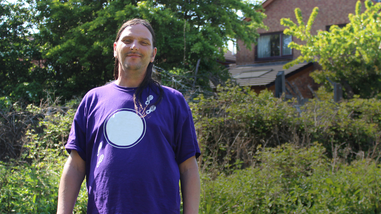 John standing in a garden wearing a purple t-shirt