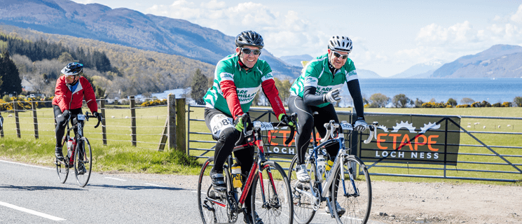 Two men in Macmillan cycling tops riding in front of Loch Ness