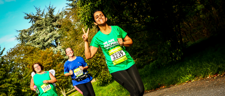Young woman wearing a green Macmillan t-shirt showing the peace sign to the camera with two other women running behind her.