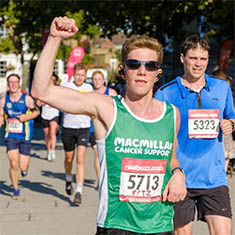 A Team Macmillan runner with red hair. They are wearing a green running vest and pumping their fist in the air.