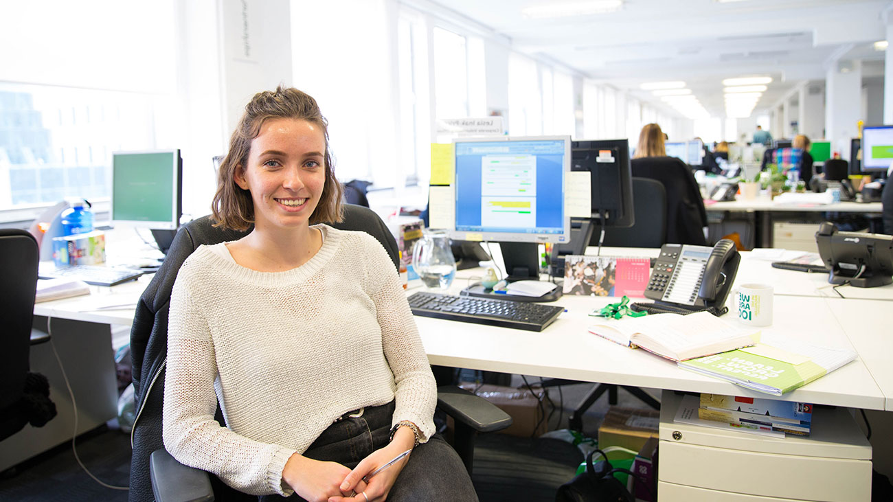 A female Macmillan intern manager sits in an office smiling.