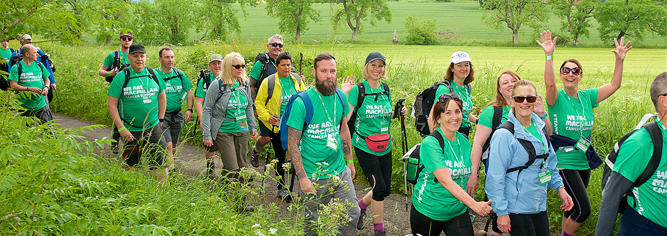A big group of walkers in green Macmillan tshirts, walking down a country path with fields and trees in the background.
