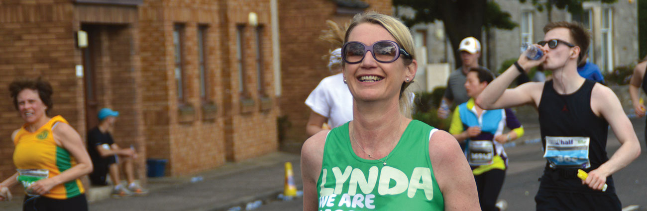 A white woman running in a marathon, wearing sunglasses and a Macmillan green vest with the name Lynda on it. She is smiling.
