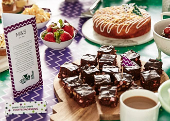 A table covered with a selection of cakes, berries and a mug of coffee. A M&S information card stands to the left.