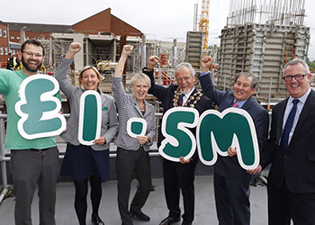 Six people, smiling and throwing their fists triumphantly into the air, holding a sign saying '£1.5 m'.