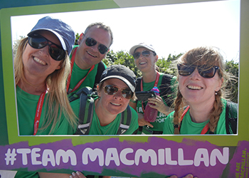 Five Macmillan fundraisers posing behind a cardboard picture frame which says #teammacmillan.