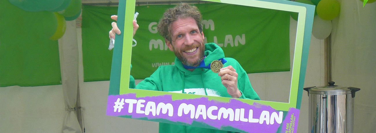 A man wearing a medal and holding a large frame around him with the words 'Team Macmillan'.