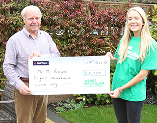 An older man wearing shirt and trousers and young woman wearing a green Macmillan vest holding up a giant cheque.