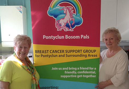 Two older women standing next to a large colourful promotional stand that contains information for a Breast Cancer Support Group.