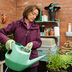 Sal, a woman diagnosed with breast cancer, waters the plants in her garden