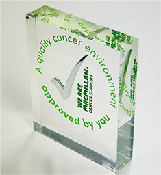 The MQEM award a solid glass plaque with a tick mark and the words 'a quality cancer environment approved by you' in a circle around it and the Macmillan logo next to it.