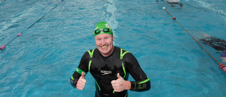 Man standing in a swimming pool wearing a wetsuit and green Macmillan swimming hat, giving two thumbs up to the camera