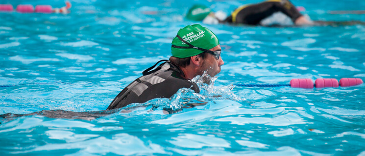 Man swimming in an outdoor pool wearing a wetsuit, goggles and a green Macmillan swimming hat