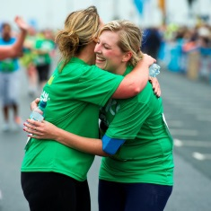 Two people with long blonde hair tied back wearing green Macmillan T-shirts and hugging.
