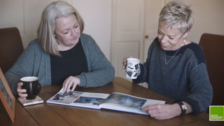 Marie and one of her relatives looking at a family photo album