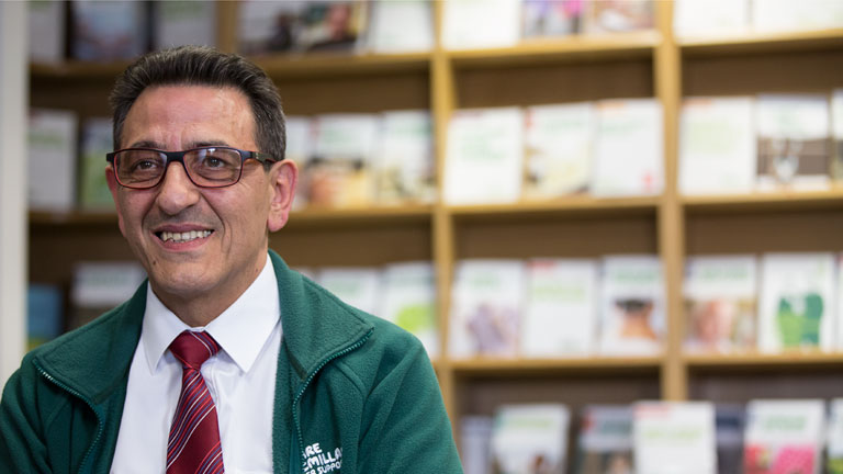 Mario, a middle-aged man wearing glasses, is sitting in front of shelves with cancer information booklets.