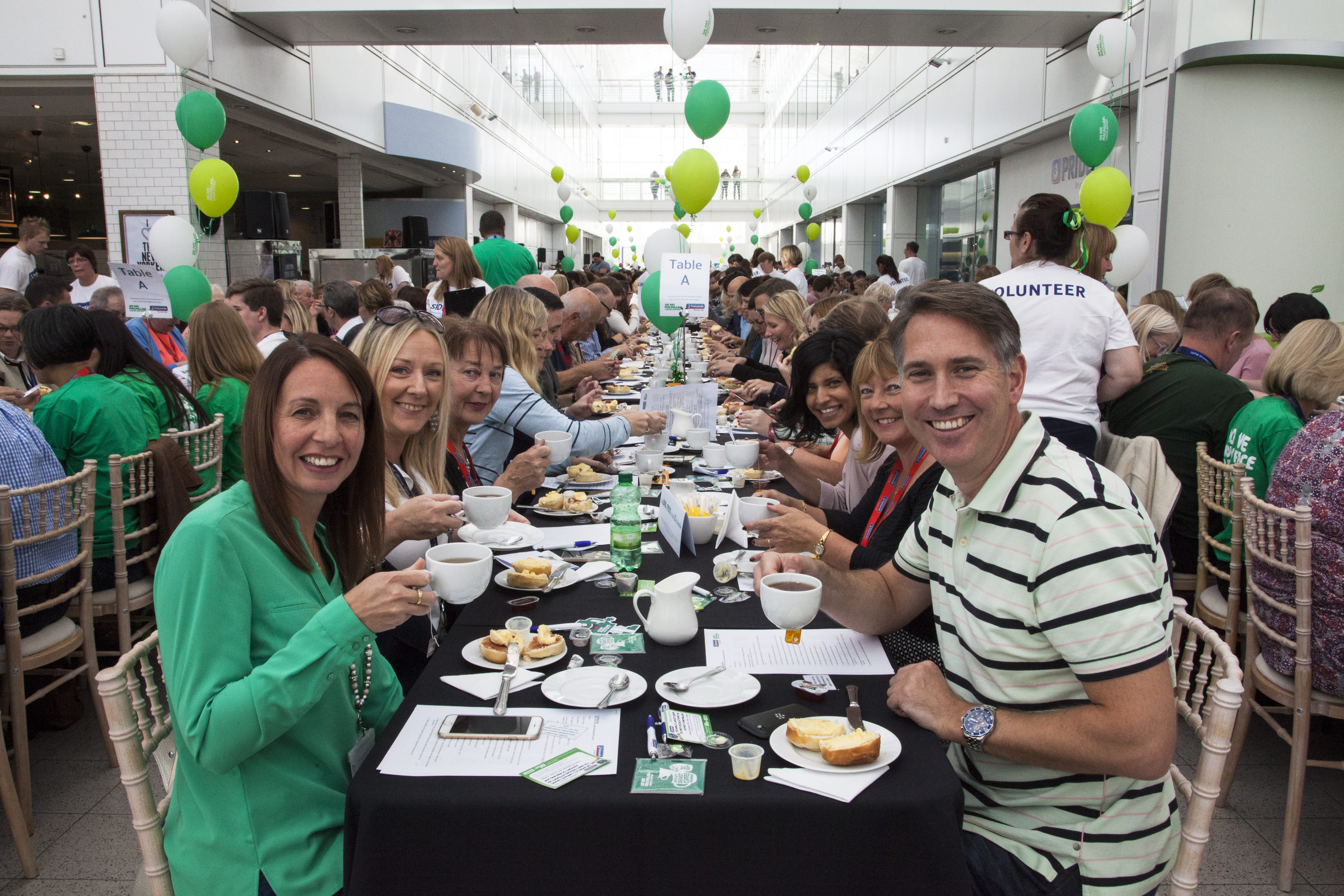 Nationwide staff sit at long tables have tea and cake at a fundraising event