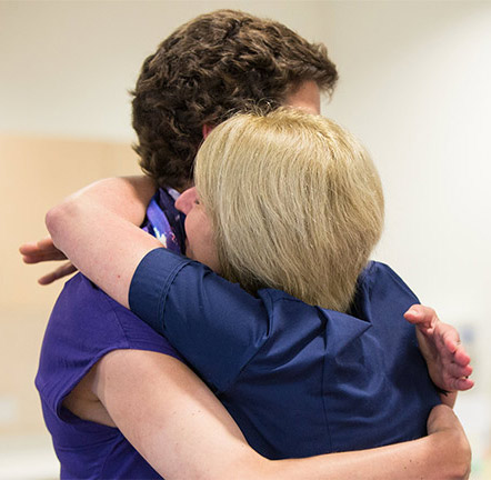 A Macmillan nurse hugging a person affected by cancer. Both their faces are turned away from the camera.
