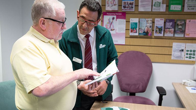 Paul looks at a Macmillan brochure with support officer, Mario.