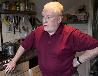 A man stands in a kitchen thinking. He has one hand rested on his hip.