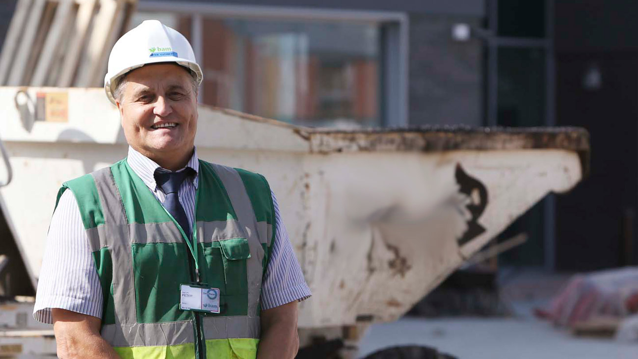 Peter, a construction worker, standing on a building site and smiling. The words 'cancer isn't fair but your boss has to be' appear next to him.